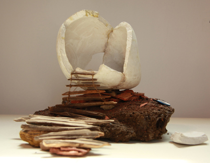 "Melanie Vote, ""Head as Home (Maquette)"", unfried clay, cowpie, found objects and materials, 10 x 10 x 12 inches, 2010"
